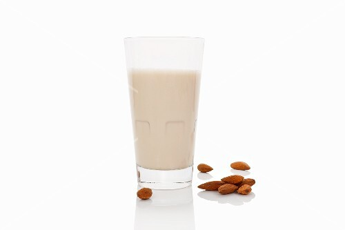 A glass of almond milk on a white surface