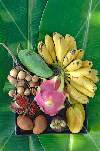 A bowl of tropical fruit on banana leaves