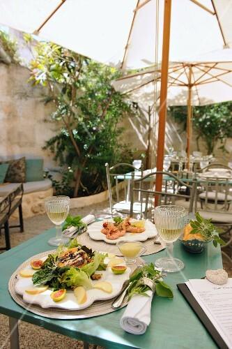 Tables laid under a parasol in a Mediterranean courtyard