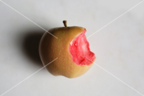 A pink pearl apple with a bite taken out of it on a marble surface