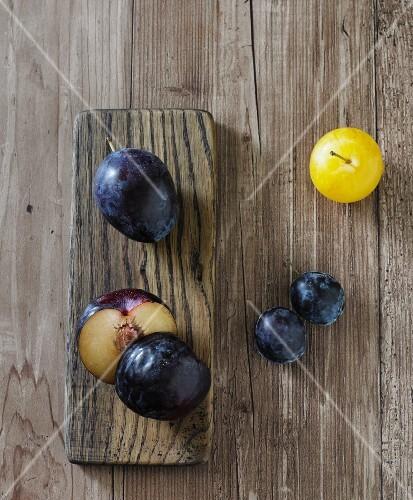 Various plums (black plums, a yellow plum, Italian plums)