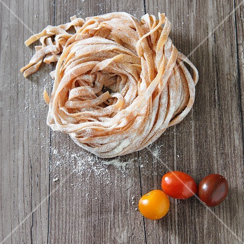 Homemade tomato pasta and fresh cherry tomatoes on a wooden surface