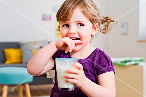 A little girl with pigtails holding a glass of milk