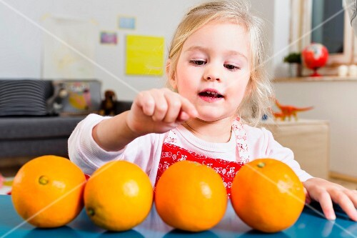 A little girl sitting at a table counting oranges