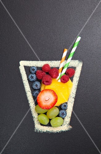A chalk drawing of a glass filled with real fresh fruit and straws