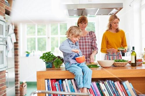 Mutter mit Kindern beim gemeinsamen Kochen in der Küche