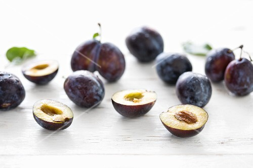 Fresh plums, whole and halved, on a white wooden surface