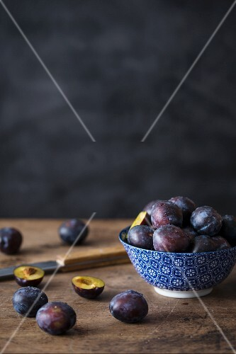 Fresh plums in a ceramic bowl and next to it