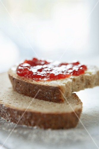 Slices of rye bread spread with jam with a bite taken out