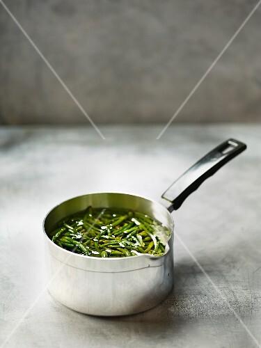 Samphire in oil in a saucepan
