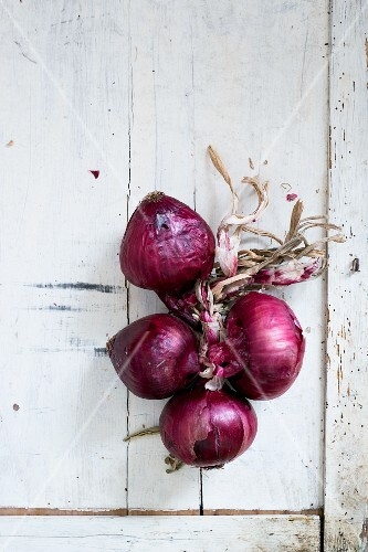 Red onions on a white wooden table