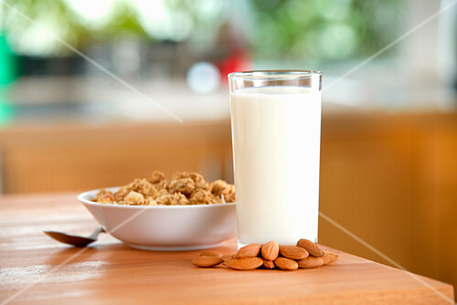 A glass of almond milk, almonds and cereals