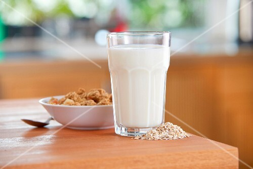 A glass of oat milk, oats and cereals