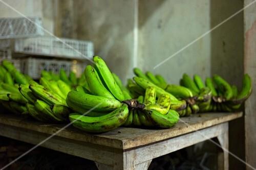 Grüne Bananen auf Holztisch auf einem Markt in Bali