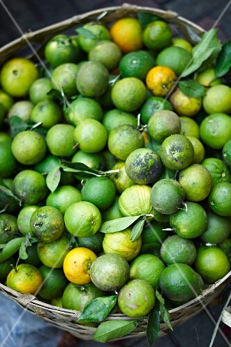 Green oranges in a basket at a market