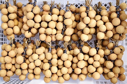 Bunddles of longans in crates at a market