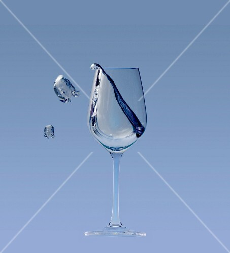 A white wine glass with a splash on a blue background