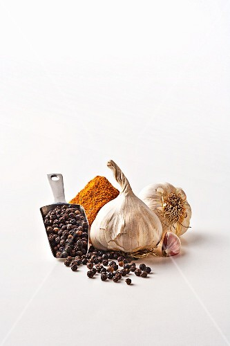 Garlic and spices on a white surface