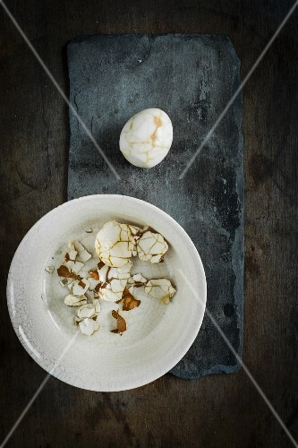 A peeled pickled egg with a linen patter on a slate surface with egg shell in a ceramic bowl on a wooden surface