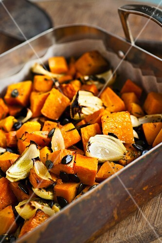 Baked pumpkin and onions, garnished with toasted pumpkin seeds and herbs