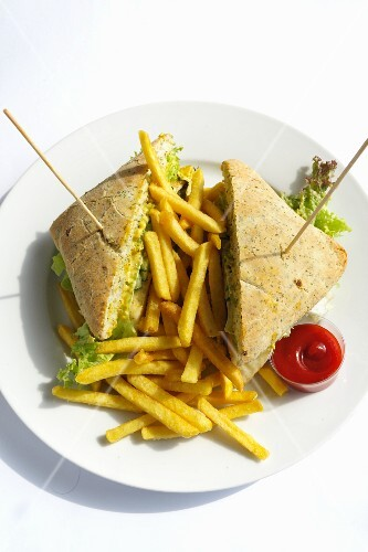 A club sandwich with chips and ketchup on a plate