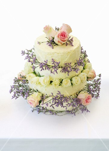 A four-tier wedding cake decorated with roses