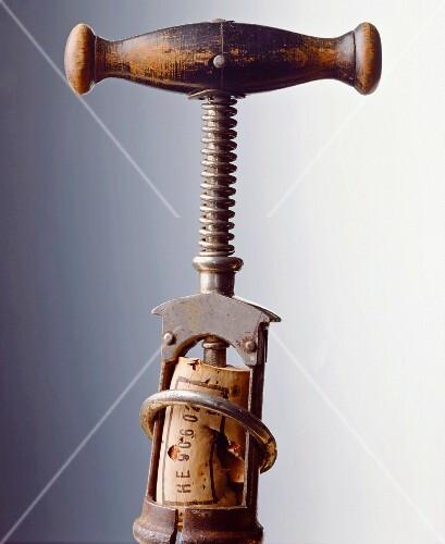 An antique corkscrew with a cork