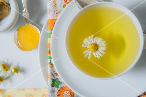 A cup of chamomile tea with a chamomile flower (seen from above)