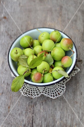 A bowl of little green apples