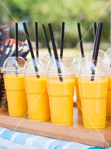 Mango lassis in take away plastic cups sold on a market stall