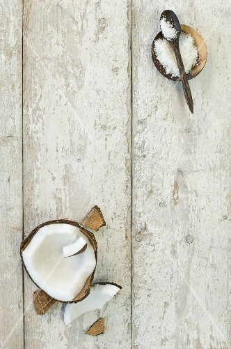 A broken coconut and coconut flakes in a wooden bowl