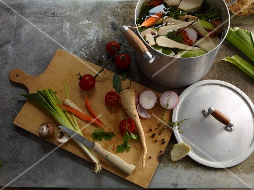 ingredients for vegetable stock on a wooden board and in a pot