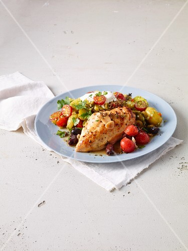 Chicken breast baked on a tray with a potato and tomato salad with pesto