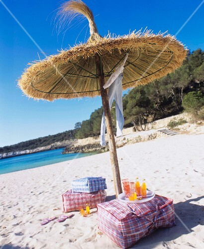 Floor cushions & drinks under straw parasol on sandy beach