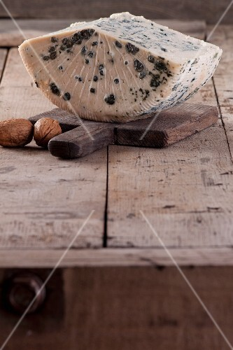 A slice of blue cheese on a wooden board