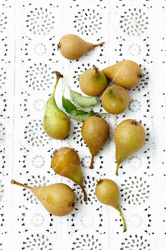 Fresh green pears on a lace surface