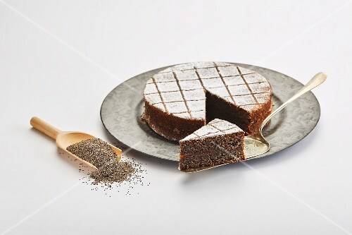 Poppyseed cake and poppyseeds on a wooden scoop