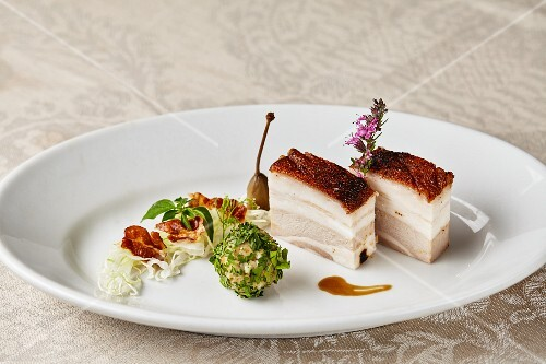 Crispy pork belly with loveage dumplings and warm bacon and cabbage salad