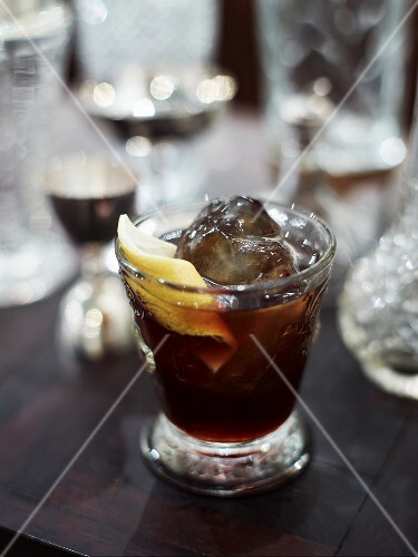 A glass of cola with ice and a slice of lemon