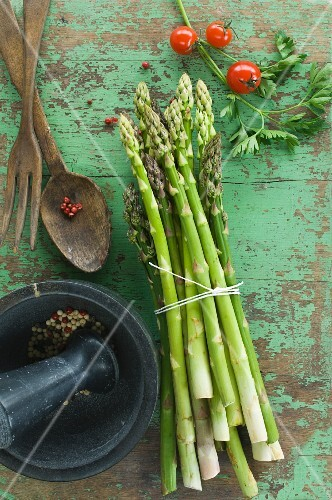 A bundle of fresh green asparagus, tomatoes and parsley on a wooden table, peppercorns in a mortar and salad servers