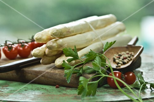 A bundle of white asparagus on a chopping board with a knife, peppercorns, parsley and cherry tomatoes