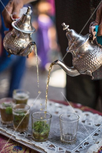 Peppermint tea being poured from silver teapots into tea glasses