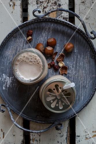 Vegan hazelnut milk in glasses with lids on a tray