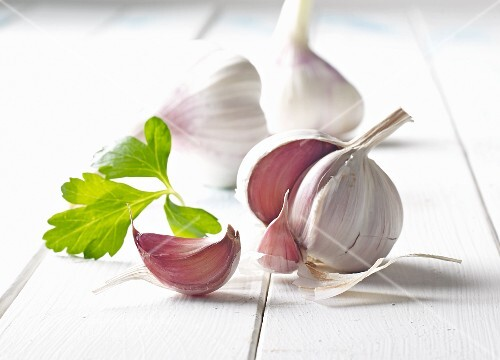 Bulbs of garlic on a white wooden surface