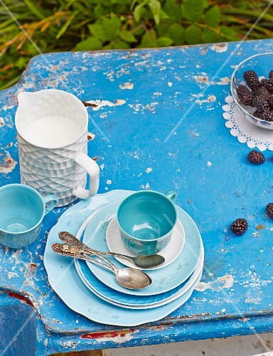A table laid with coffee crockery, blackberries and milk in a garden