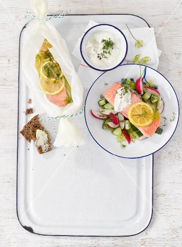 Oven-baked salmon on a cucumber and radish salad with a herb dip and wholemeal bread