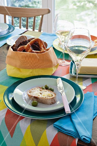 A table laid with colourful acceccories, bread, olives and white wine