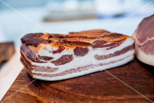 A piece of smoked bacon on a wooden board