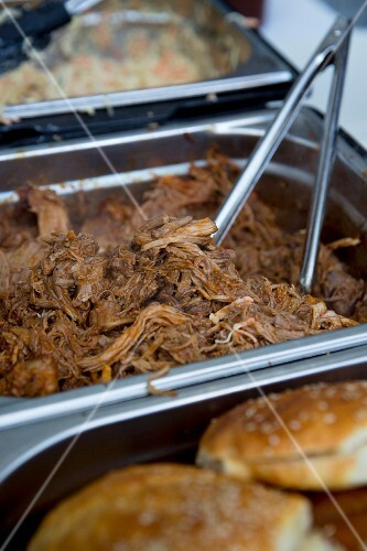 ingredients for pulled pork buns in metal containers at a fast food stall