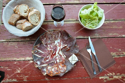A rustic meat platter with bread, red wine and lettuce